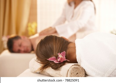 Conceptual image of getting massage in salon, flower in womans hair in focus.?