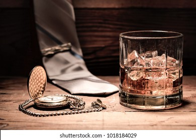 A conceptual image of a glass of liquor, a pocket watch, and a neck tie.