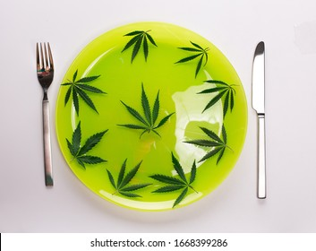Conceptual image of green cannabis leaves on a light green plate with a knife and fork isolated on white background with copy space for text. Say no to drugs take natural herbal herbs medicine concept