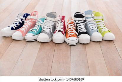 Conceptual image of gumshoes sneakers shoes on vintage wood floor in different sizes, lifestyle concept.