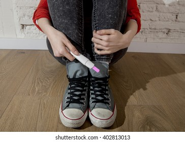 conceptual image hand of pregnant teenager girl or young desperate woman holding positive pink pregnancy test sitting on home floor in unwanted baby and unexpected motherhood concept