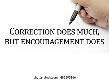 Conceptual image of handwriting quotes CORRECTION DOES MUCH,BUT ENCOURAGEMENT DOES with the hand and pen isolated in white background. copy space . Quotes concept.