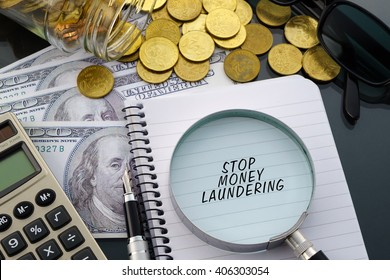 Conceptual image with hundred dollar bills, coins, calculator, notepad and magnifying glass with word Stop Money Laundering.