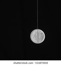 Conceptual image of Indian coin hangs on a string