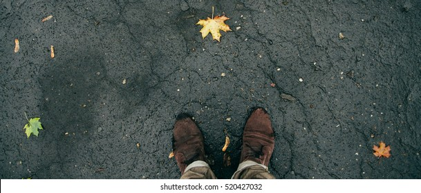 Conceptual image of legs in boots on the autumn leaves. Feet shoes walking in nature. Square image.Outdoor with Autumn leaves on background Lifestyle Fashion concept.