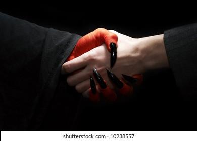 ?conomic conceptual image. Male businessman handshake with devil. Dark contrast lighting