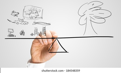 Conceptual image of a man drawing a seesaw balancing the effect of urbanisation, industry and technology versus nature and the ecology placing them in equilibrium.
