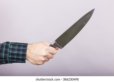 Conceptual image of a man holding a big sharp knife over gray background