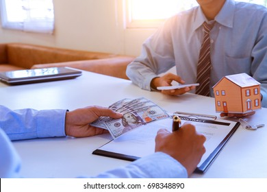 Conceptual image of a man signing a mortgage or insurance contract or the deed of sale when buying a new house or selling his.