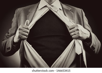 Conceptual image of a man tearing off his shirt over gray background