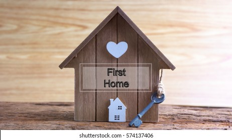 Conceptual image of miniature home icon made from wood and word written FIRST HOME on wooden base.Selective focus.
