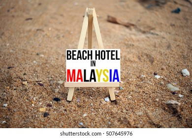 conceptual image on a sandy beach with word BEACH HOTEL IN  MALAYSIA with red, yellow and blue color font on white canvas frame with wooden tripod stand. Selected focus sand at the beach