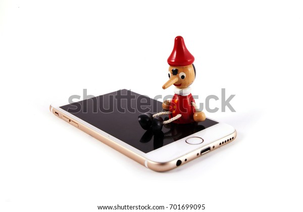 Conceptual image, Pinocchio doll with mobile phone. Concept of customer support lies.