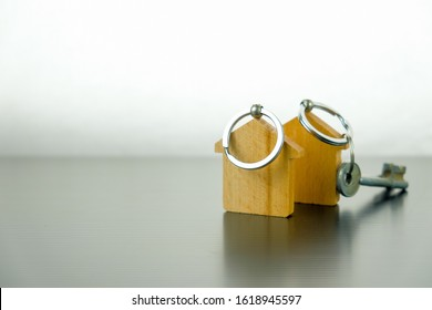 Conceptual image of property keys handover. Isolated wooden key chains on reflective table. Silver keys in blur. Focus on key chain holder upfront.