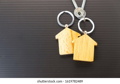 Conceptual image of property keys handover. Isolated wooden key chains on dark table. Focus on key chain holder.