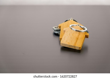 Conceptual image of property keys handover. Isolated wooden key chains on reflective table. Silver keys in blur. Focus on key chain holder.