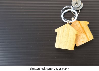 Conceptual image of property keys handover. Wooden key chains on dark table. Silver keys in blur. Focus on key chain holder.