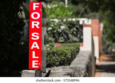 Conceptual image of red Real Estate For Sale sign advertising Private Property House or Apartment, blurred residential background, copy space.