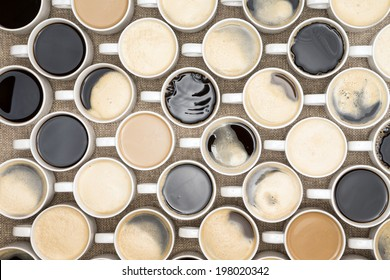 Conceptual image of regimented rows of coffee mugs lined up in straight rows with their handles facing the same direction like coffee soldiers, overhead view with black, espresso, latte and cappuccino