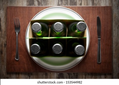 Conceptual image representing alcoholism on a funny way using a six-pack of beer bottles for dinner.