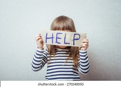 Conceptual image of a sad dejected little girl with a pouting lip standing holding a handwritten HELP sign