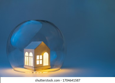 Conceptual image of safety when staying at home during Corona virus COVID-19 quarantine lockdown. Toy house protected by glass bowl.