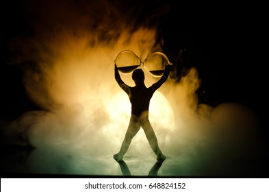 Conceptual image with sandglass and and man with moon at background with fog. Silhouette of toy figure touching hourglass. deadline concept. Man rising hands