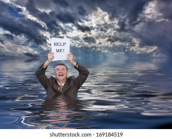 Conceptual image of senior businessman in suit up to waist in deep water worried about drowning in paperwork and holding help me document. Stormy clouds behind reflect in the ocean.