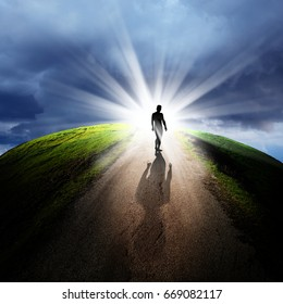 conceptual image of silhouetted man on empty road over cloudy sky with beam of light