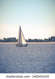 Conceptual image of a single sail boat on a peaceful blue lake.