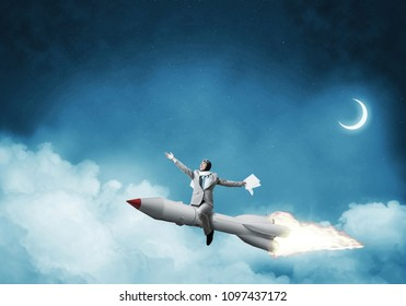 Conceptual image of successful businessman in suit flying on jet rocket with blue night skyscape with clouds and moon on background.
