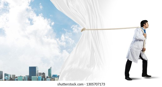 Conceptual image of successful doctor on white medical suit pulling white curtain while standing on white background with urban city view behind white fabric