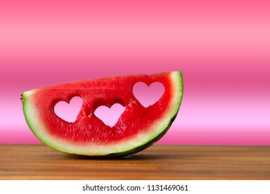 Conceptual image of summer with watermelon with heart shapes with copy space. With pink gradient color background.