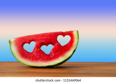 Conceptual image of summer with watermelon with heart shapes with copy space. With blue gradient color background.