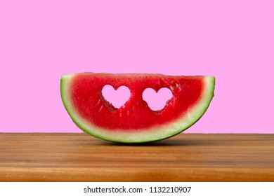 Conceptual image of summer with Watermelon with heart shapes. Pink background with copy space.