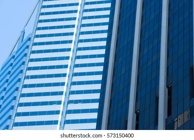 Conceptual image of textured facade of modern design skyscraper office buildings in city business centre, reflection in futuristic window surface pattern background and copy space.
