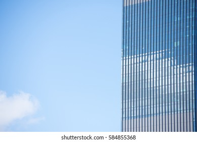 Conceptual image of textured window facade of modern design skyscraper office buildings in city business district, reflection in window surface pattern background, blue sky and copy space.