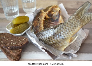 Conceptual image: vodka with a stockfish and newspaper with pickled cucumber and bread on an shabby table.