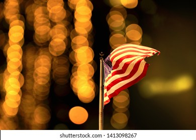 Conceptual image of waving American flag over abstract lights
