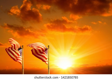 Conceptual image of waving American flags at tall poles in a row over orange colored sunset sky