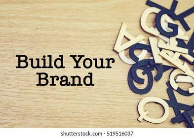 conceptual image, word BUILD YOUR BRAND on wooden background. alphabet word on the right