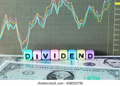Conceptual image of the word dividend on letter cube with stock graph and dollar background.