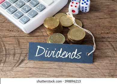 Conceptual image of the word Dividends written on label tag with coins,dice and calculator