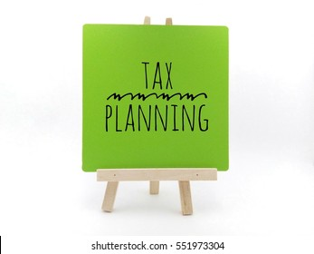 "Conceptual image with word ""tax planning"" on green frame and wooden tripod"