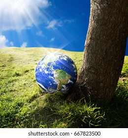 conceptual image of world on green landscape. NASA furnished globe image layered and used