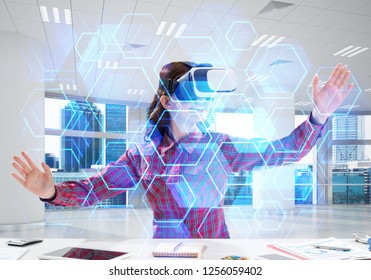 Conceptual image of young and beautiful woman in checkered shirt using virtual reality headset and interracting with media interface while sitting inside bright office building.