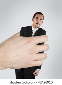 Conceptual image of a young business man in hand of something that hurts (crisis ,bankruptcy, boss, mortgage, debt, etc)