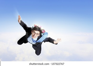 Conceptual image of young businessman flying with parachute on back