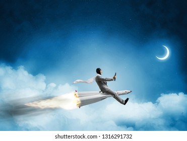 Conceptual image of young businessman in suit flying on rocket with blue night skyscape with clouds and moon on background.