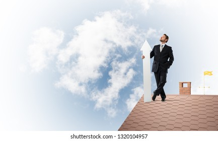 Conceptual image of young businessman in suit looking upside and holding big white arrow in hand while standing on brick roof with cloudy skyscape view on background.